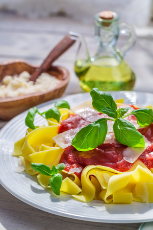 Homemade pappardelle pasta with tomato sauce and parmesan photo