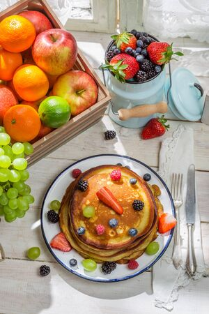 Tasty pancakes with fruits and maple syrup photo
