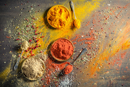 Vivid spices and herbs on old table
