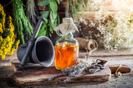 witchdoctor: Therapeutic herbs in bottles with herbs and alcohol