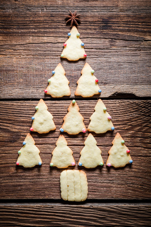 cake decorating: Freshly baked Christmas tree arranged with gingerbread cookies Foto de archivo