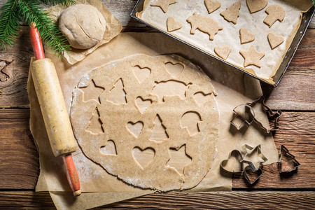 gingerbread cookie: Cutting gingerbread cookies for Christmas Stock Photo