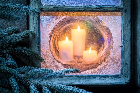 candle: Burning candles for Christmas in frozen window at eve Stock Photo