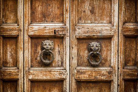 puertas de hierro: Puerta de madera r�stica con los golpeadores como fondo