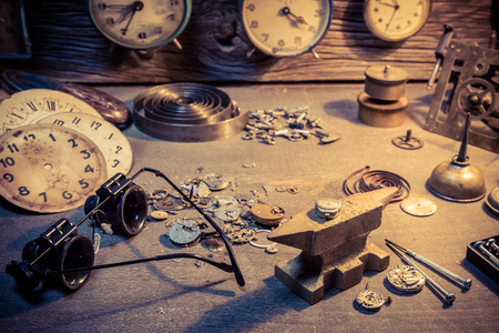 antique background: Old watchmakers workshop with parts of clocks