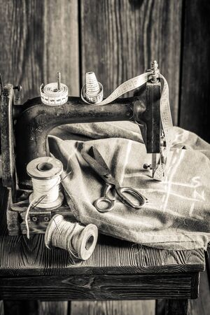 clothing shop: Vintage sewing machine with threads, scissors and cloth Stock Photo