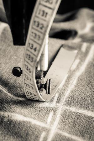 Vintage kleermaker machine met een schaar, draden en doek Stockfoto