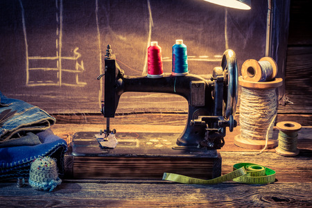 Vintage tailor workshop with sewing machine, cloth and scissors Imagens