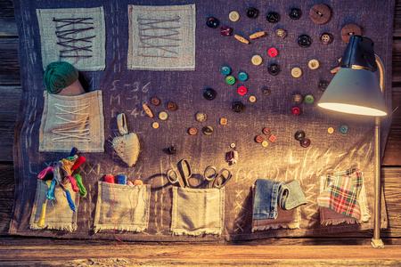 coser: paño de costura con tijeras, hilos y agujas en el taller de sastre