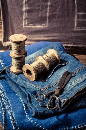 bespoke: Closeup of cloth, needle and scissors in tailor workshop Stock Photo