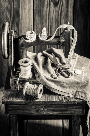Old tailor machine with scissors, cloth and threads Stock Photo