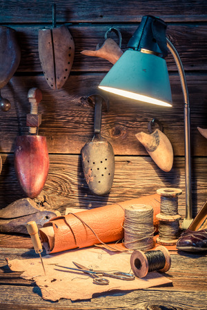 Vintage cobbler workshop with shoes, laces and tools Reklamní fotografie