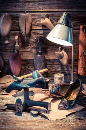 Vintage shoemaker workshop with tools, leather and shoes Stok Fotoğraf - 54735557