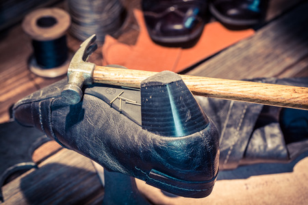 cobbler: Cobbler workplace with brush and shoes Stock Photo