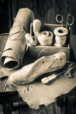 Small shoemaker workshop with tools, shoes and laces Stock Photo