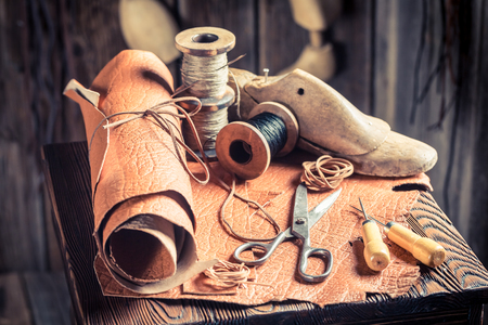 Aged cobbler workplace with tools, shoes and laces Stockfoto