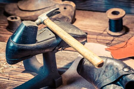heel strap: Vintage shoemaker workshop with brush and shoes Stock Photo