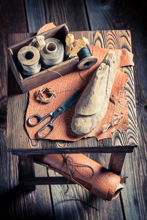 heel strap: Small cobbler workshop with tools, shoes and leather