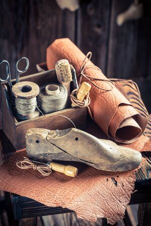 heel strap: Small shoemaker workshop with tools, leather and shoes Stock Photo