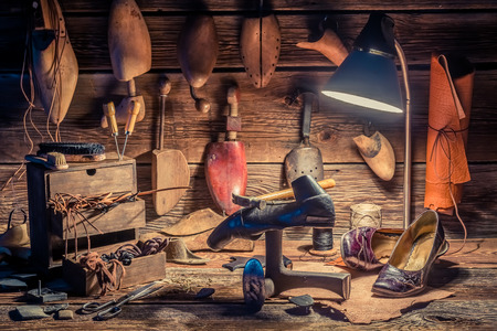 cobbler: Vintage shoemaker workplace with brush and shoes