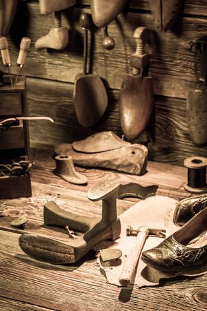 heel strap: Cobbler workshop with tools, shoes and leather Stock Photo