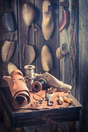 heel strap: Aged cobbler workplace with tools, shoes and leather Stock Photo