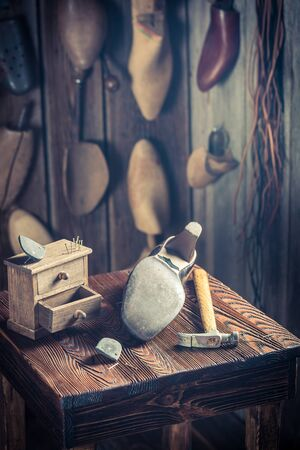 Aged shoemaker workplace with brush and shoes Foto de archivo