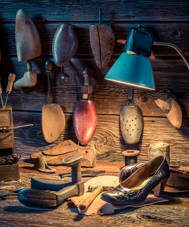 heel strap: Shoemaker workshop with tools, shoes and leather