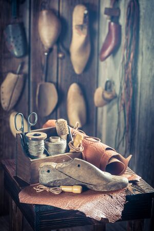 heel strap: Small shoemaker workshop with tools, shoes and leather Stock Photo