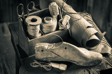 Small shoemaker workplace with tools, shoes and laces