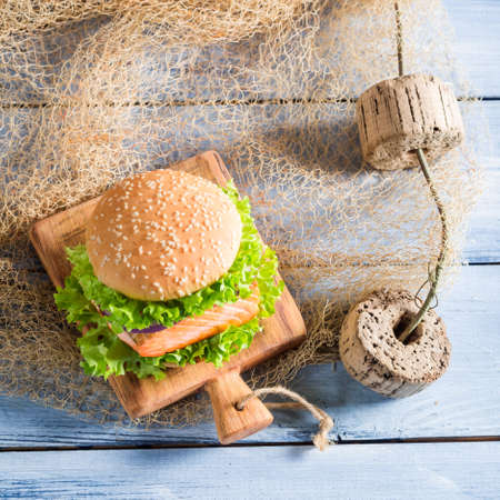 salmon fishery: Homemade burger with fish and vegetables on fishing net Stock Photo