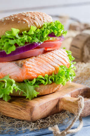 salmon fishery: Closeup of homemade burger with big fish and vegetables Stock Photo