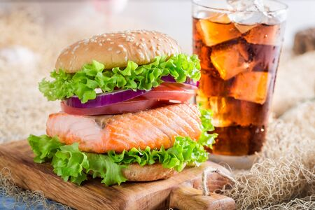 salmon fishery: Closeup of fresh burger with fish served with cold drink