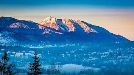 january sunrise: Foggy Zakopane and lighted peak at dawn in winter, Tatra Mountains, Poland Stock Photo