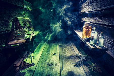 Witch hut with potions, scrolls, books and blue, green smoke with copy space for Halloween Stock Photo