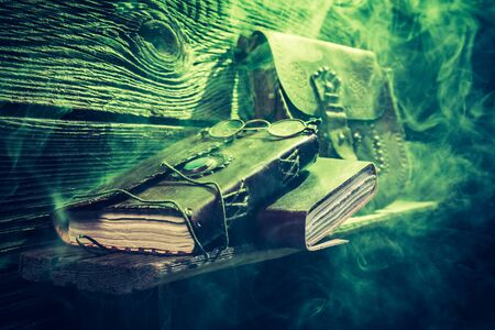 medieval medicine: Vintage witcher cottage with green light and books for Halloween Stock Photo