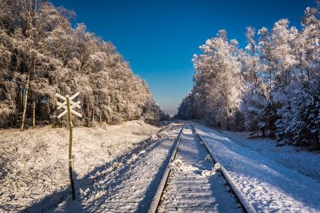 Frozen unused railway line in winter at sunrise