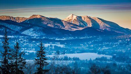 december sunrise: Foggy Zakopane and illuminated peak at dawn in winter, Tatra Mountains, Poland