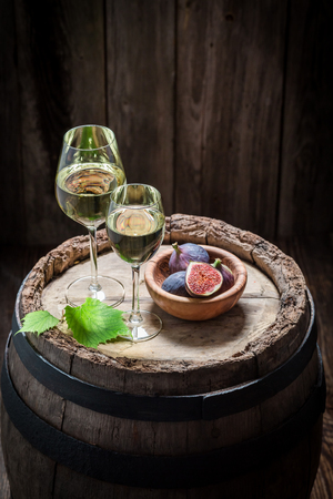 Tasty white wine with figs on old barrel