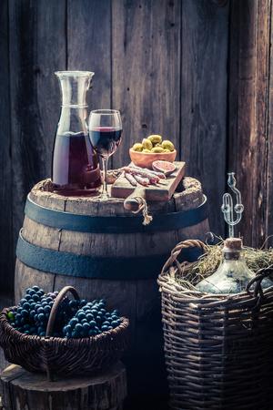 vino tinto casero con aceitunas, embutidos, uvas y damajuana Foto de archivo