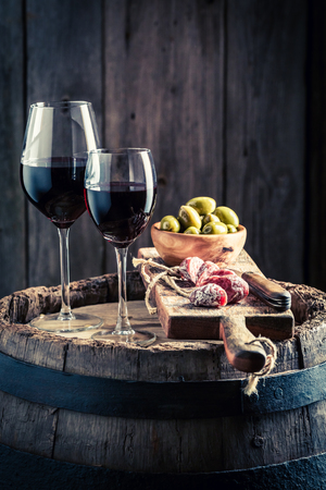 Tasty wine in glass with cold meats and olives on wooden board Stock Photo