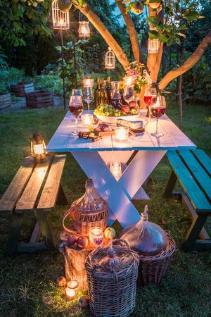 ワインや夕暮れ時の庭でキャンドルでゴージャスなテーブル 写真素材