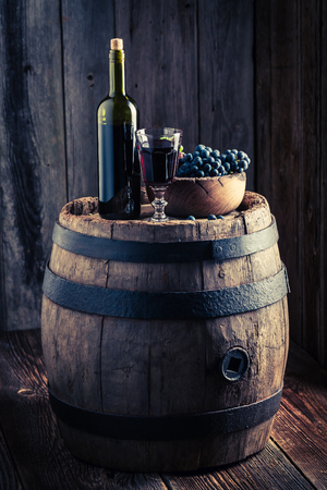 Glass full of wine with fresh grapes on wooden barrel Stock Photo