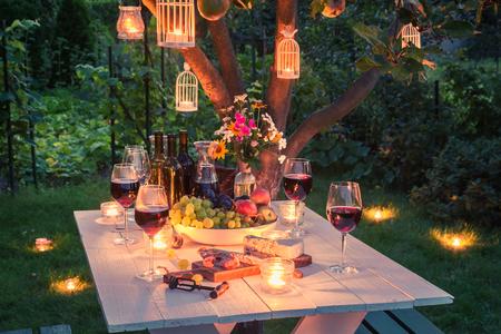 チーズと肉の夕暮れ時の庭の美しいテーブル 写真素材