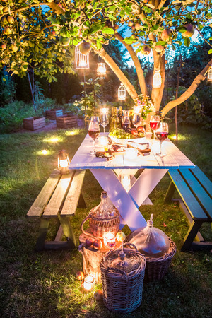 Gorgeous table full of cheese and meats in garden at dusk