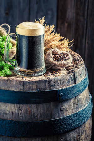 unbottled: Fresh and cold dark beer on wooden barrel with hops and wheat