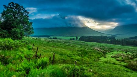 스코틀랜드의 Glencoe 산들 위에 안개가 자욱한 새벽