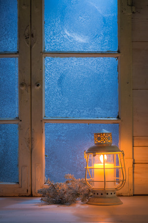 frosted window: Frosted window at night with burning candle for Christmas