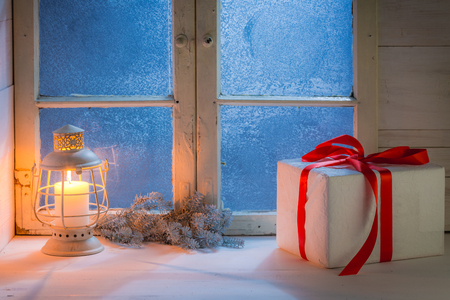 frosted window: Frosted window with burning candle for Christmas at night Stock Photo