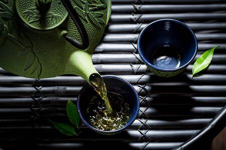 黒いテーブルの上のアジア レストランでおいしい緑茶 写真素材